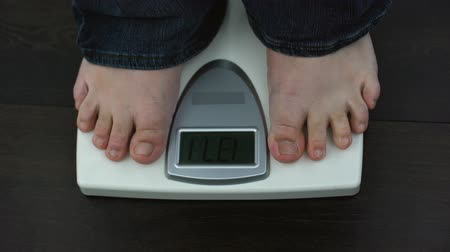 tartmak : Overweight male feet on weighing scales, measuring kilograms after workout Stok Video