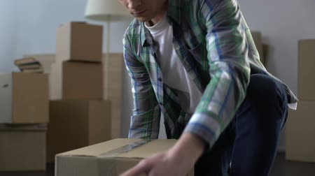 coisas : Young man packing boxes with stuff, moving from apartment, end of rent contract