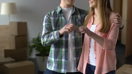subsidie : Happy couple showing keys from new apartment to camera, moving in together