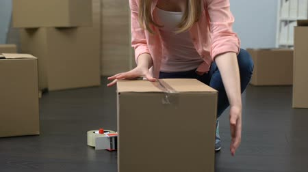coisas : Lady from moving service carefully packing boxes with stuff and carrying out