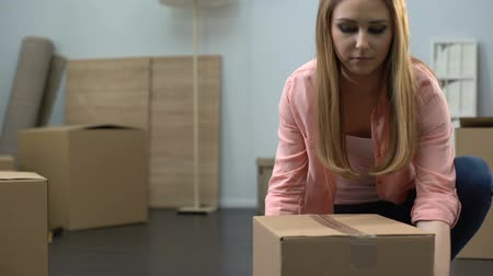 provést : Lady packing things in box, moving company worker carrying baggage, moving out Dostupné videozáznamy