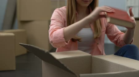 liquidação : Female student unpacking things in dormitory, looking at parents photo, family Stock Footage