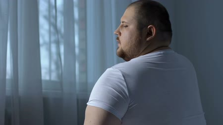 sedentary : Lazy obese man exercising shoulder muscles, rheumatology disorder.
