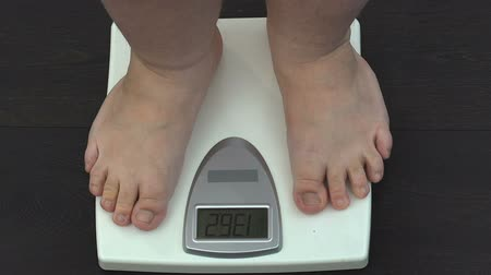 kilogramm : Obese man measuring weight on scales at home, slimming training program, health