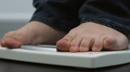 kilogramm : Fat male legs in jeans standing on scales, everyday weight measuring.