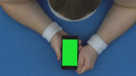 スリミング : Sportsman watching online fitness video, lying smartphone on mat, workout break