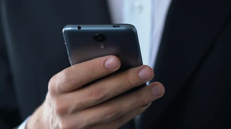 e mail : Hand of businessman holding smartphone checking personal mail box.