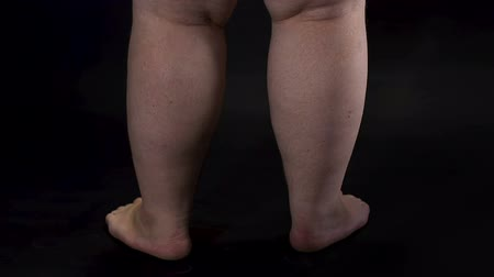 упитанность : Obese male legs turning around dark background, body care, unhealthy nutrition Стоковые видеозаписи