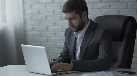 decidir : Pensive businessman typing on laptop, nervous about difficult startup solution Stock Footage