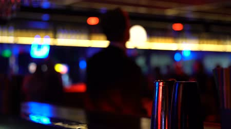 зависать : Man drinking whiskey and dancing at bar counter, relaxation on Friday night