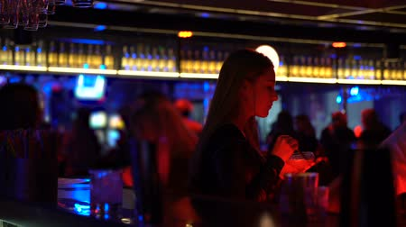 зависать : Attractive woman drinking cocktail at bar counter, enjoying music, nightlife