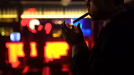 striptease : Young businessman smoking cigar, looking at women dancing, nightlife for rich