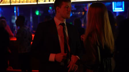 зависать : Young couple moving to music at disco club, relaxing at night party together