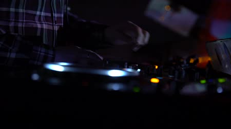 tweaking : Hands of male dj turning controls on sound equipment, playing music in nightclub