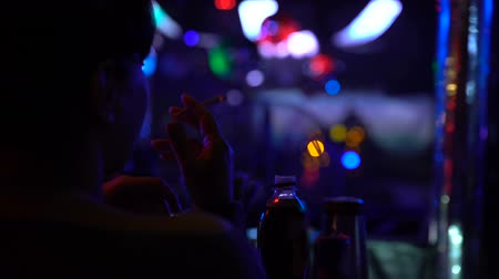 bad habits : Back view of woman sitting at bar counter and smoking cigarette at night club Stock Footage