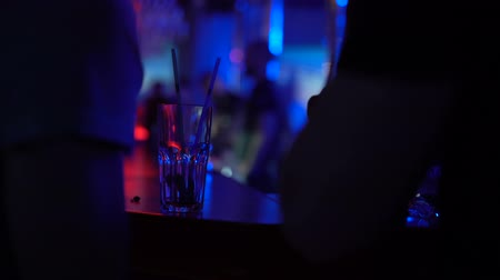 artigos de vidro : People standing at bar counter and chatting, close-up of empty glass, nightclub Stock Footage