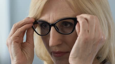 půvabný : Self-assured mature woman prinking herself, putting on glasses looking in mirror