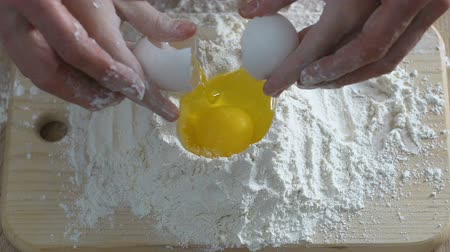 кухонная посуда : Child and grandmother adding egg to flour, family cooking, home traditions Стоковые видеозаписи