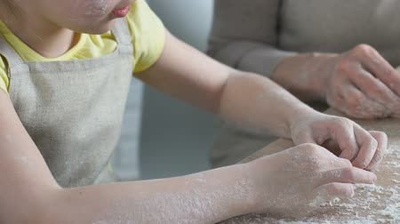 вкусности : Touching girl carefully helping her grandmother to mold dough, home traditions Стоковые видеозаписи