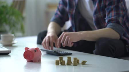 копилку : Man calculating money, putting coins into piggy bank, family budget planning