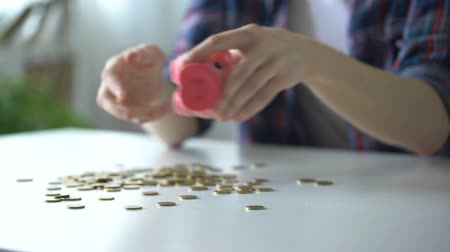 tirelire : Teenager pouring out coins from piggy bank, not enough money for dream purchase