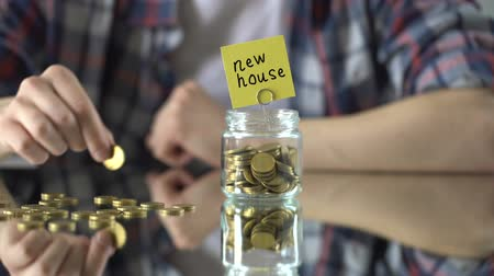 escrito : New house phrase above glass jar with money, saving concept, moving, immigration Vídeos