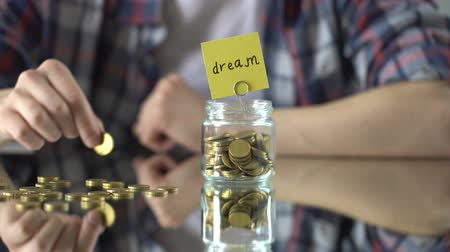 save : Dream word written above glass jar with money, savings for hobby, interests