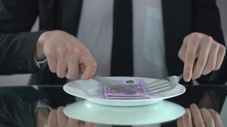 ganancioso : Businessman eating euro banknotes, squandering concept, embezzlement of budget