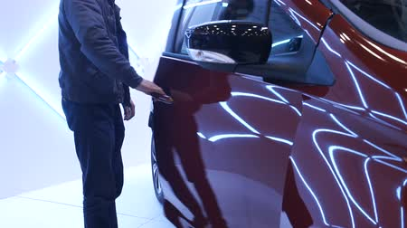 getting electricity : Illuminated futuristic car, man getting inside, exhibition of exclusive vehicles Stock Footage