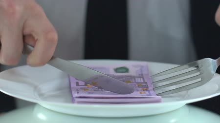 enflasyon : Rich male eating banknotes with fork, concept of consumer society, greedy person Stok Video