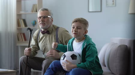 végső : Grandpa and grandson cheering for favorite football team, happy for winning Stock mozgókép