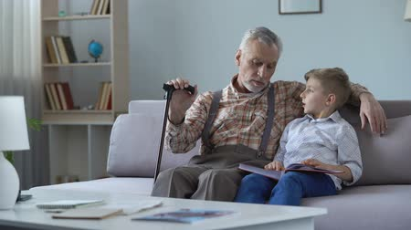remember : Grandpa watching photo album with grandson, remembering youth, telling stories Stock Footage