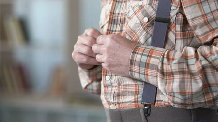 deterioration : Old man with trembling hands buttoning up shirt, beginning of Alzheimer disease