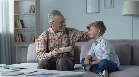 loved : Caring grandson giving present to grandpa, attention and care for loved ones Stock Footage