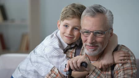 avó : Grandson cuddling grandfather with love, precious family minutes, elderly care