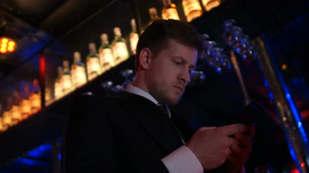 tárcsázás : Busy man in classic suit texting with someone on smartphone at night club, app Stock mozgókép
