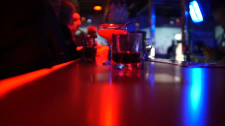 vermouth : Variety of cocktails on bar counter, people communicating at night club party