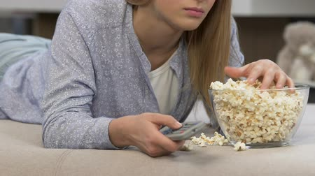 znuděný : Girl eating popcorn and watching boring tv programmes, television consumerism