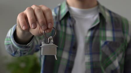 bugiganga : Male hand holding key chain house close-up, mortgage loan, rent of apartment