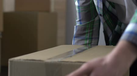 incapacidade : Man packing cardboard box with adhesive tape, moving out, migration, life change Stock Footage