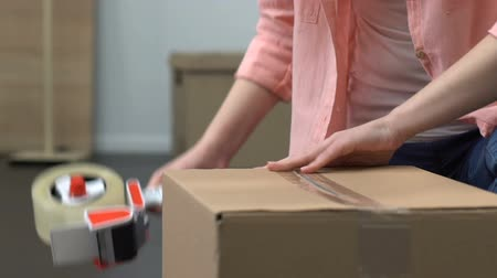 проданный : Girl packing stuff in box, moving, delivery service worker helping on background