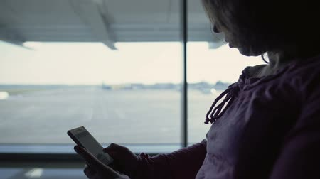 chegar : Female tourist reading online book, waiting for flight, spending time in airport Vídeos
