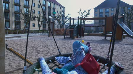 kopenhagen : Dreaming adult woman swinging in hanging seat, relaxing on vacation, memories