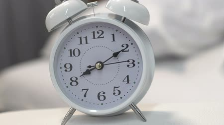 напоминать : White alarm clock standing on table near bed, deadline, time management, closeup Стоковые видеозаписи