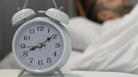 deprivation : Alarm clock sound waking up male sleeping in bed, self-discipline and morning