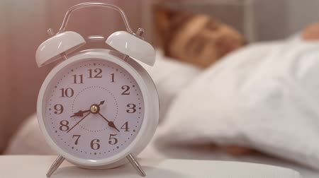 probudit se : Sleep interruption, alarm clock ringing near bed with sleeping male student