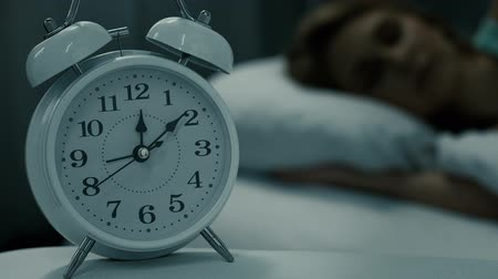deprivation : Woman sleeping in bed at night, white alarm clock standing on table.