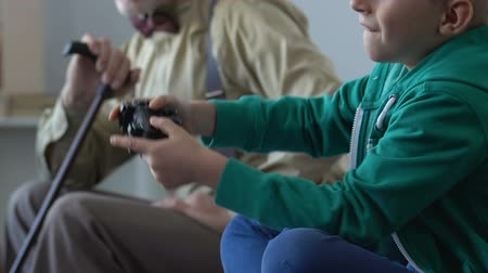 misunderstanding : Sad grandfather sighs while his grandson playing video games, generation gap