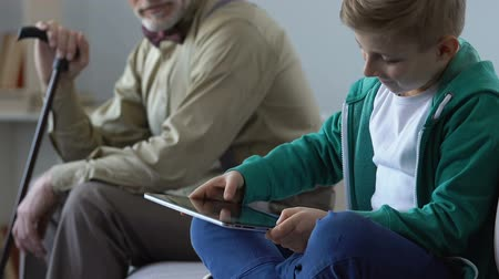 criticize : Addicted boy playing tablet game and sad grandfather looking him.