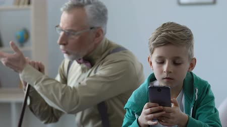scold : Angry old man scolding grandson playing smartphone game, family misunderstanding